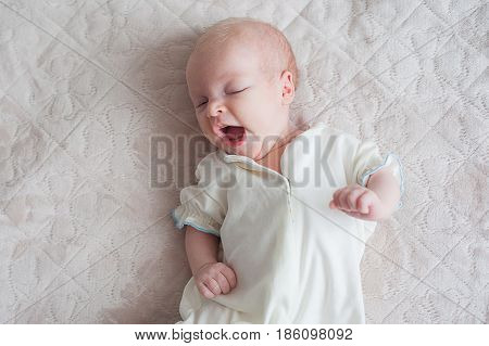 Cute baby girl yawns on a white background Newborn on bed