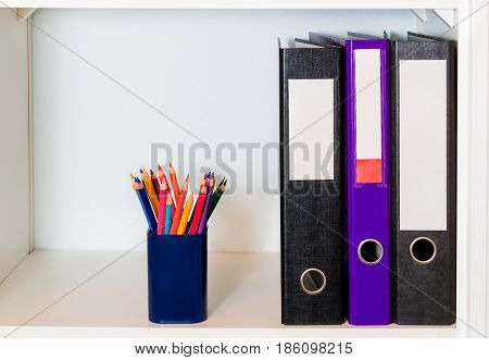White office shelf with folders and pencil holder