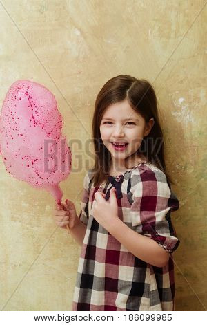 Happy adorable girl small little child in plaid dress smiling with delicious pink cotton candy sweet sugar spun candyfloss on stick on beige background. Unhealthy food or snack