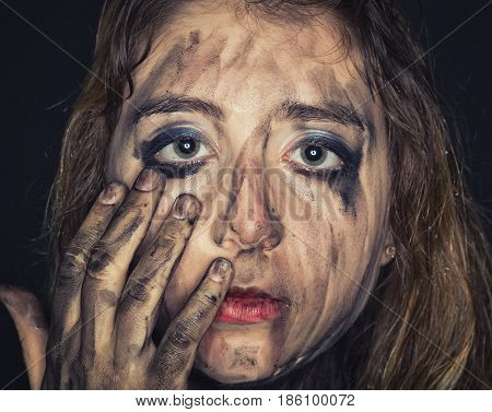 Sad young woman with dirty face and arms on dark background