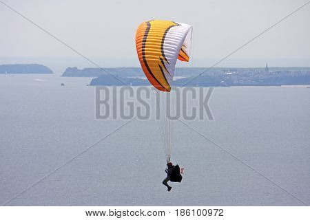 Paraglider flying above the coast of Pembokeshire