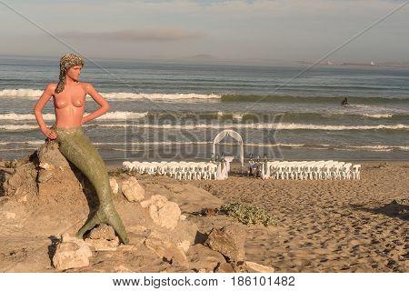 LANGEBAAN SOUTH AFRICA - APRIL 1 2017: Preparations for a wedding under the watchful eyes of a mermaid on the beach at Boesmanland Plaaskombuis in Langebaan in the Western Cape Province