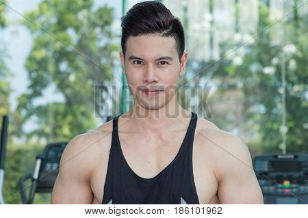 Handsome muscular sports man portrait looking at camera he has sweat on face after exercise