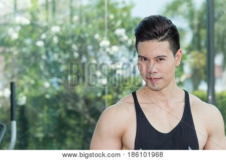 Handsome muscular sports man portrait looking at camera and copy space he has sweat on face after exercise