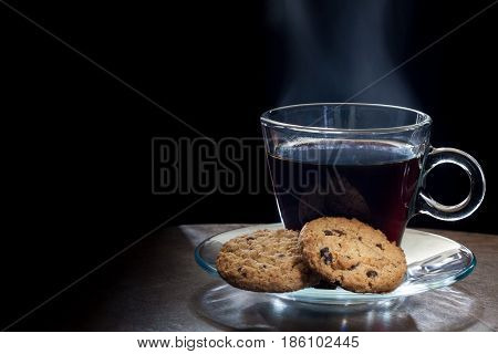 Steaming hot black coffee with chocolate chip cookies on black background