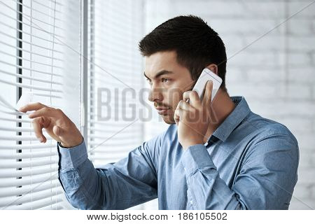 Businessman calling on phone and looking through blinds