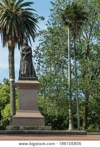 Auckland New Zealand - March 5 2017: Black metal statue of Queen Victoria on stone footing framed by green trees in Albert Park under blue sky.