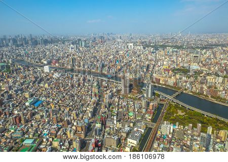 Aerial view of Tokyo city skyline with Asahi Beer Hall, Asahi Flame o Golden Turd, Sumida River Bridges and Asakusa area from Tokyo Skytree observatory. Daytime. Tokyo, Japan.