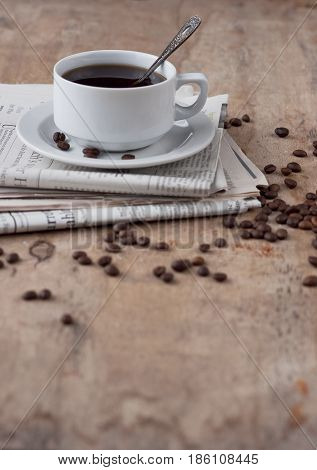 A cup of black coffee on a wooden table with scattered grains and newspaper. Black coffee Hot drink Grains Newspaper Wooden background White cup Breakfast