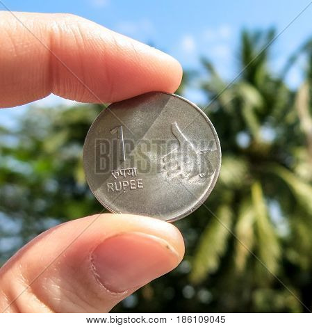 Femail Fingers Holding One Rupee Coin On The Green Palms Background. Personal Finance Concept. Thumb