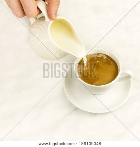 Milk poured into a cup of coffee, on a white marble background with a place for text, square photo