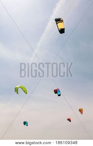Colorful kites fly in the cloudy sky