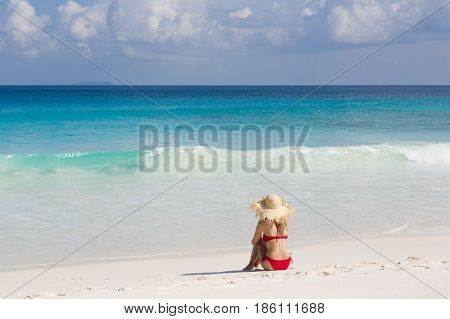 Tropical beach, turquise water and horizon. Slim blonde woman sits in red swimsuit.