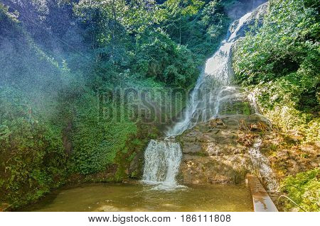 A beautiful waterfall at Sikkim India. Water is coming down passing through rocks and green vegetation and small particles of water spray creating a wet environment all over the place.