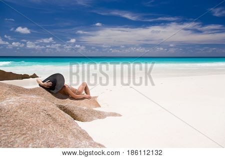 Tropical sandy beach with turquoise water, beautiful woman lays on rock in black sunhat.