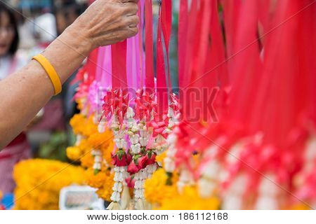 buddhist buy flowers for worship buddha statue on holy day.