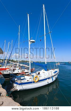 White boat with a sail on the mast at the port on a clear Sunny day. Boat reflected in a blue sea water.