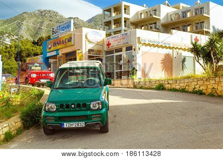 Bali Greece - may 2 2016: Rental all-wheel drive car Suzuki are parked on sloping street leading to the sea about office leasing transport. Resort village Bali Rethymno Crete Greece