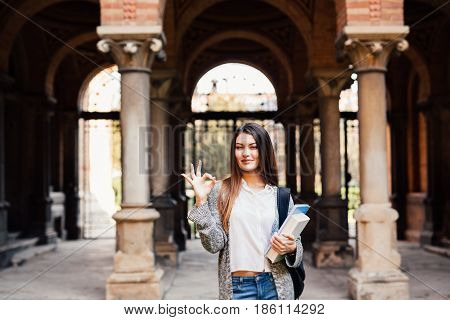 Portrait Of A Smiling Female Student Showing Okay Outdoors Near University