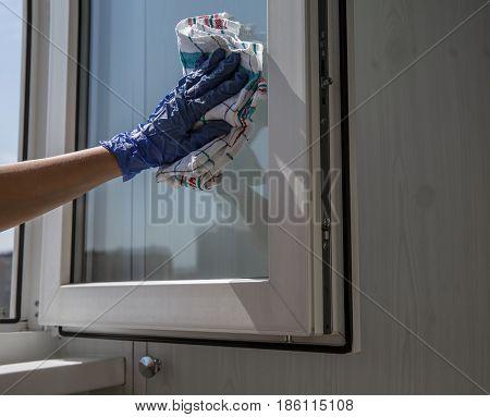 Hand in blue glove with rag washing window glass