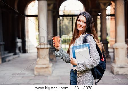 Young Beauty Student Girl With Notebooks Outdoors The University Drink A Cup Of Coffee