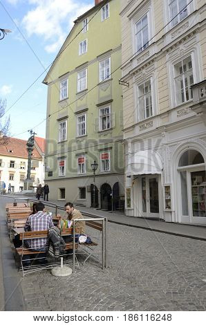 GRAZ, AUSTRIA - MARCH 19, 2017: People at outdoor restaurant in a street of the old city of Graz the capital of Styria Austria.