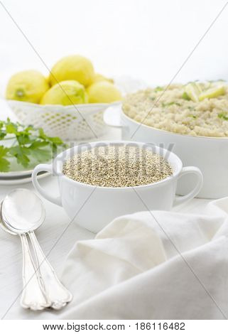 composition of uncooked Quinoa with cooked in the distances, in a vertical bright and airy image with lemons and herbs,white background for copy space