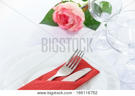 Elegant restaurant table setting for a romantic dinner with rose plates cutlery and stemware.