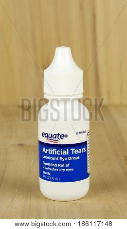 RIVER FALLS,WISCONSIN-MAY 12,2017: A bottle of Equate brand artificial tears eye drops with a wood background.