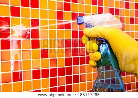 Person doing chores in bathroom at home cleaning tiled wall with spray detergent