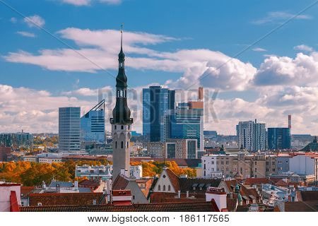 The spiers, weather vanes, the roofs of the old city on the background of modern buildings in Tallinn.