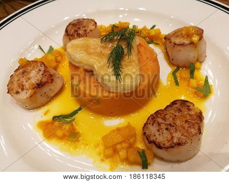 Pan fried seared Hokkaido scallop served with creamy mashed sweet potato and orange sauce top with heart pie. Special dish for celebrating Xmas New year Valentine Ester Thanksgiving and Party