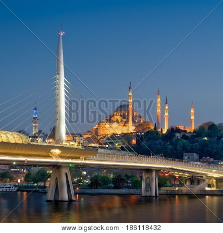 Night shot of Golden Horn Metro Bridge (Halic Bridge) overlapping Suleymaniye Mosque Istanbul Turkey