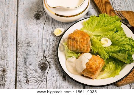 Chicken souffle, poured with sauce and leaves of fresh green salad on a white plate on a gray wooden background.