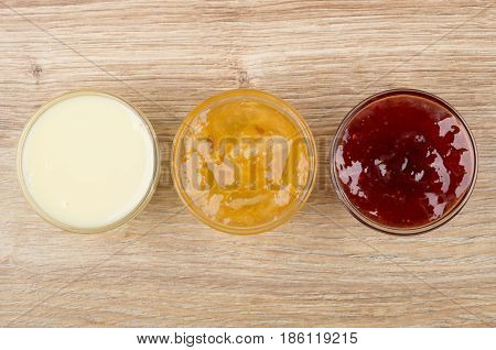 Bowls With Condensed Milk, Lemon Jam And  Strawberry Jam