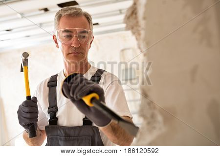 Worthy Senior Man Working With Hammer And Tool While Demolish Wall