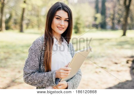 Young Woman Walking In The Park With Laptop In Hands
