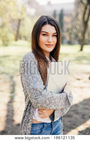 Pretty Young Woman Walking With Laptop Under The Hand In Park