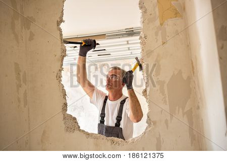 Senior Worker Using Tool At Contruction Site
