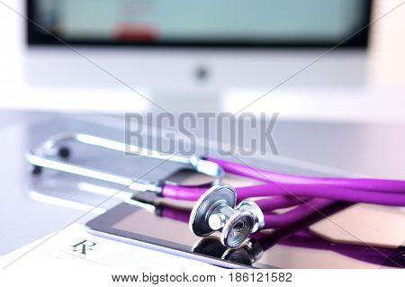 Tablet computer with a stethoscope lie on a table.