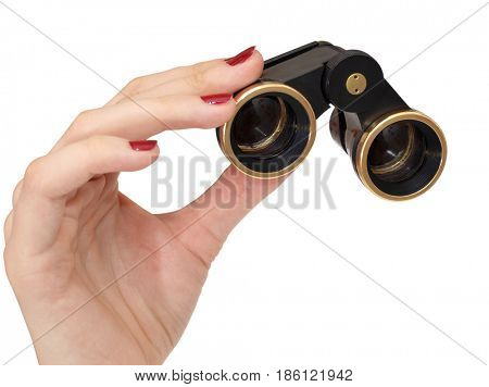 Old theatrical binoculars in a female hand on white background