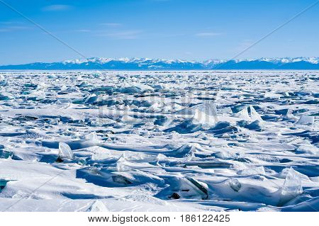 Ice hummocks of the frozen Lake Baikal, Siberia, Russia. On the other side of the lake the Khamar-Daban Range is visible