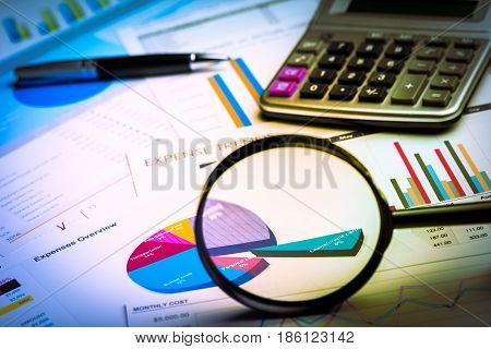 Magnifying Glass and Calculator on Business Graphs and Charts