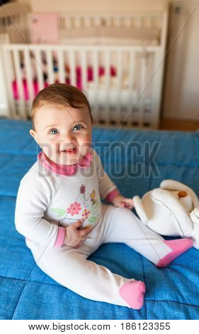 Baby Girl On The Bed With Toddler Bed In The Background.