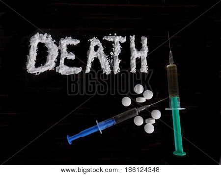 Cocaine drug powder in death word shaped, pills and injection syringe