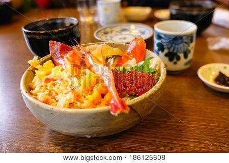 Selective focus on Rice bowl topping sea food wiith shrimp caviar salmon sashimi Uni. Japaness food.