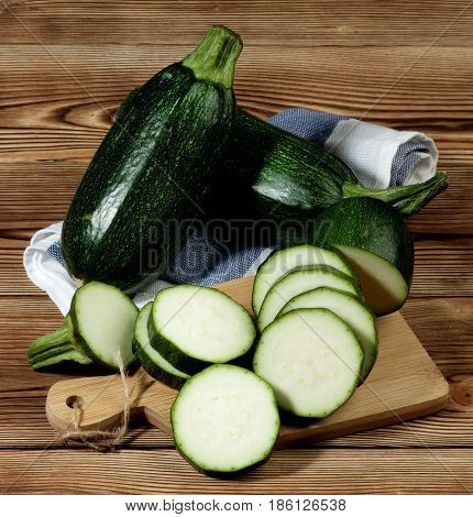 Arrangement of Fresh Ripe Zucchini Full Body and Slices on Cutting Board closeup on Wooden background