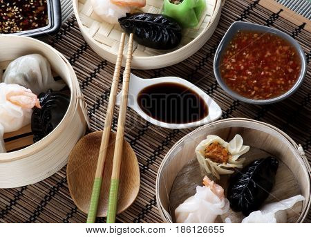 Various Dim Sum in Bamboo Steamed Bowls Chili and Soy Sauces with Chopsticks closeup on Straw Mat background