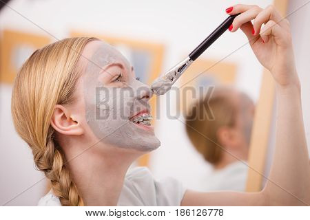 Happy Young Woman Applying Mud Mask On Nose