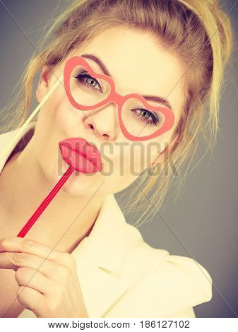 Happy elegant woman holding carnival accessoies on stick having fun at work wearing white office jacket